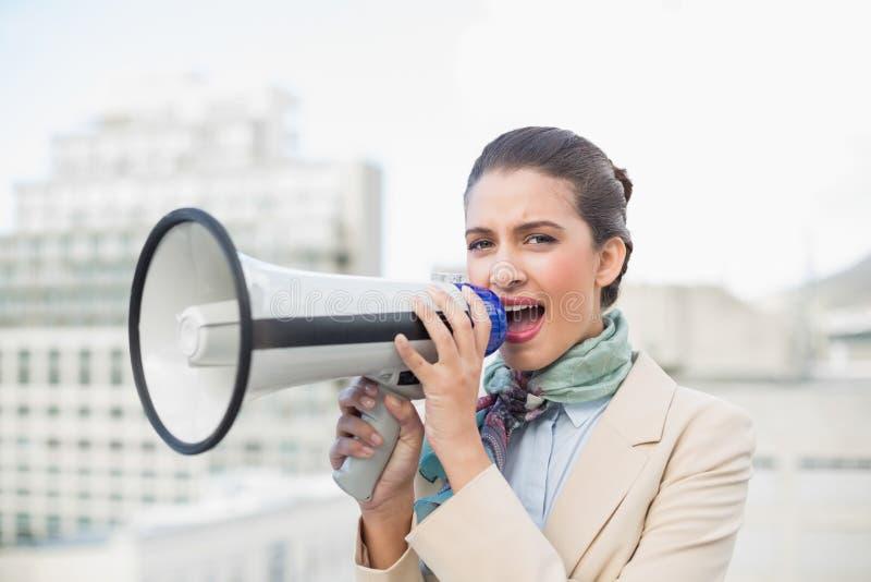 Donna di affari dai capelli marrone astuta irritata che per mezzo di un megafono immagini stock libere da diritti