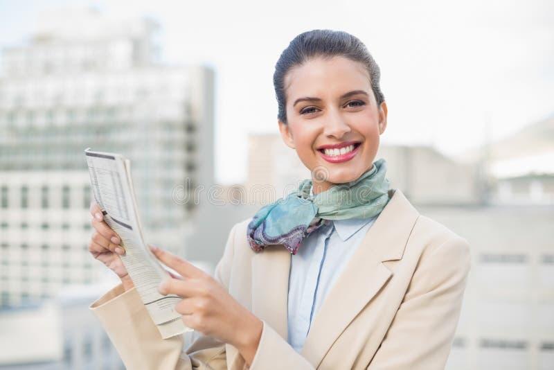Donna di affari dai capelli marrone astuta sveglia che tiene un giornale fotografia stock libera da diritti