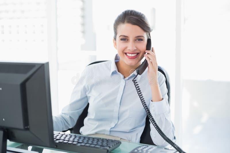 Donna di affari dai capelli marrone di classe allegra che risponde al telefono fotografie stock