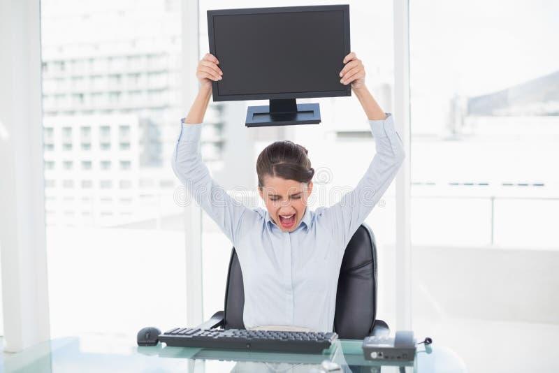 Donna di affari dai capelli marrone di classe arrabbiata che getta il suo schermo di computer fotografia stock