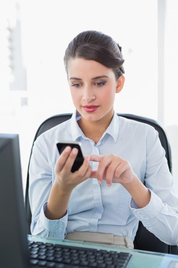Donna di affari dai capelli marrone di classe concentrata che manda un sms con il suo telefono cellulare immagini stock libere da diritti