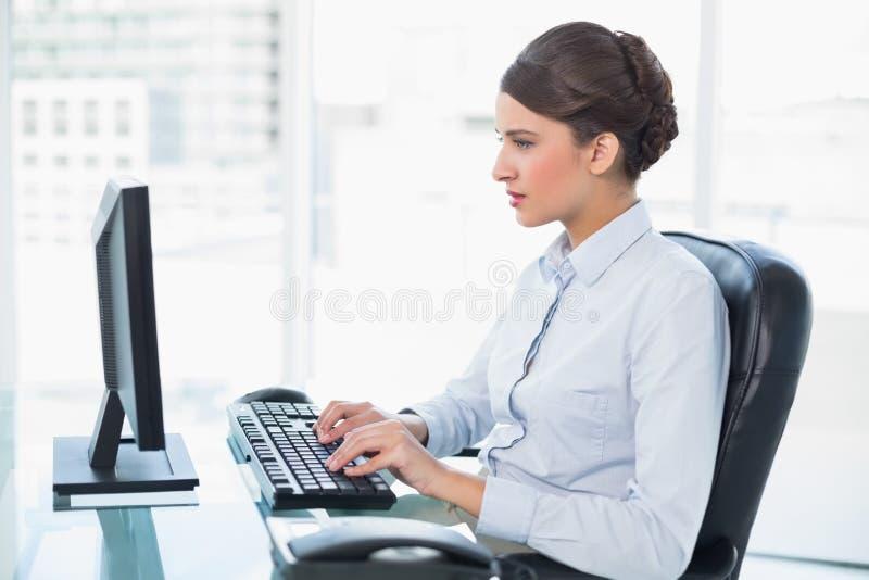 Donna di affari dai capelli marrone di classe concentrata che scrive su un computer fotografia stock libera da diritti