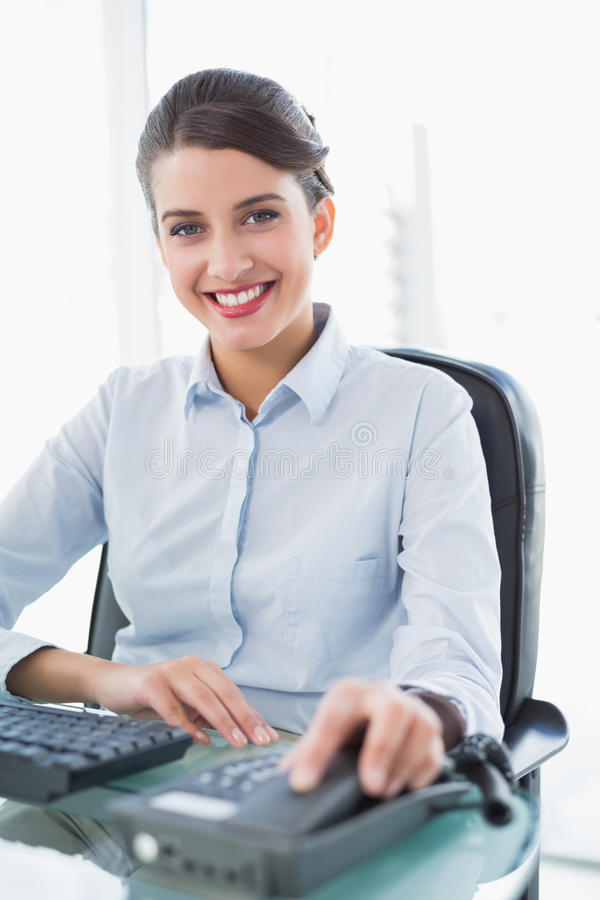 Donna di affari dai capelli marrone di classe sorridente che appende sul telefono fotografia stock