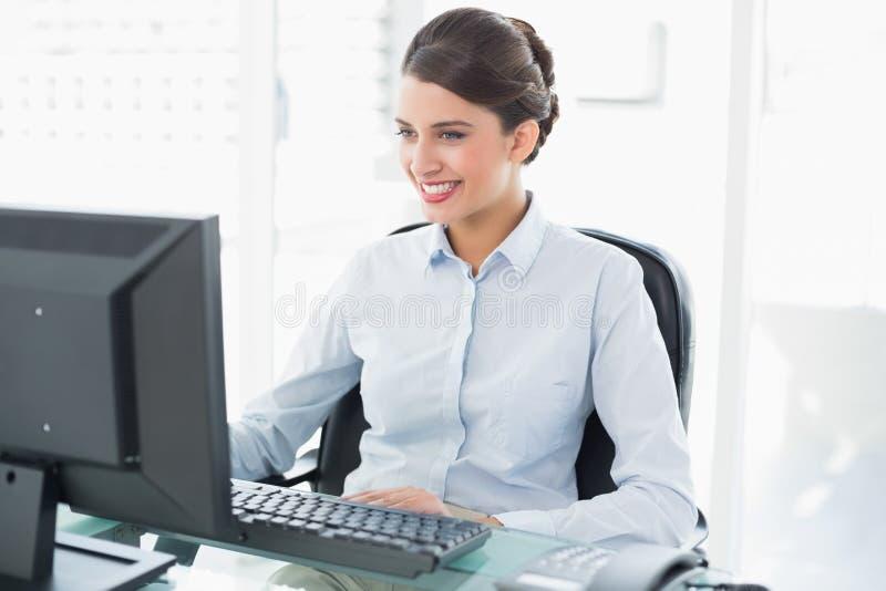 Donna di affari dai capelli marrone di classe sorridente che per mezzo di un computer immagini stock