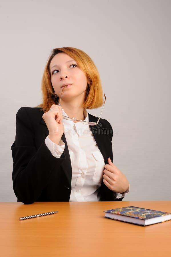 Donna di affari dai capelli rossi giovane alla tavola fotografia stock libera da diritti