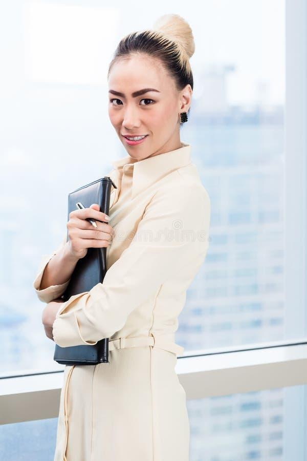 Donna di affari davanti alla finestra del grattacielo immagine stock