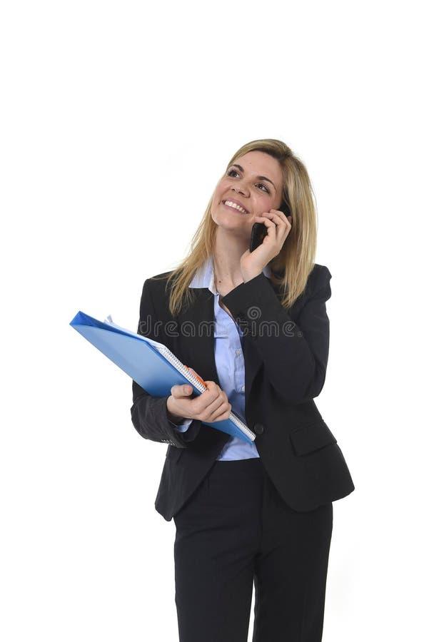 Donna di affari dei capelli biondi che parla sul sorridere della cartella e della penna dell'ufficio della tenuta del telefono ce immagini stock