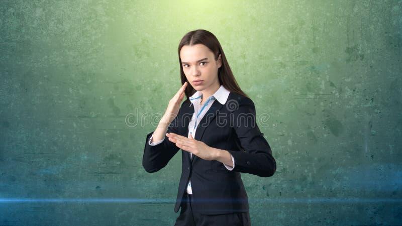 Donna di affari del ritratto del primo piano che solleva le mani nell'attacco aereo con il taglio di karatè, fondo verde isolato fotografia stock libera da diritti