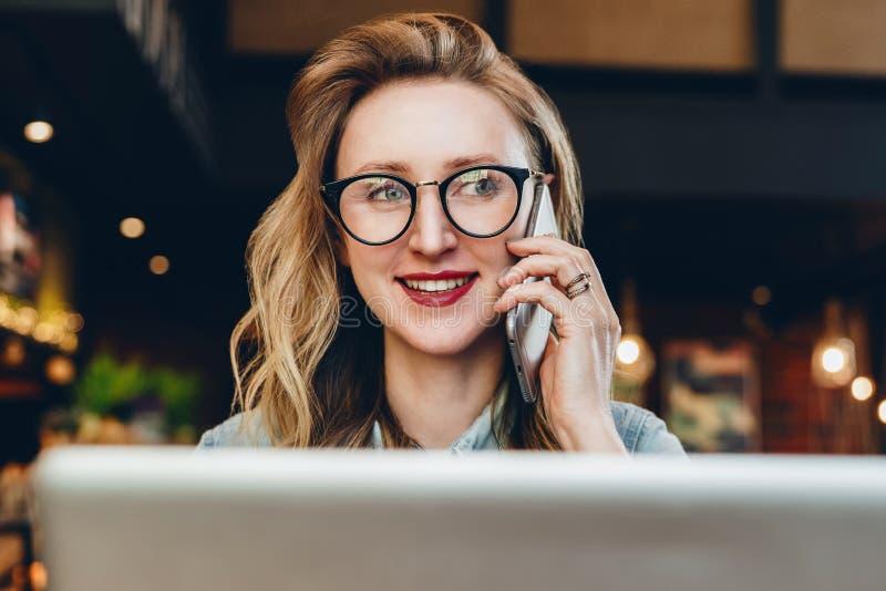 Donna di affari del ritratto in vetri che si siedono in caffè davanti al computer portatile, parlante sul telefono Il blogger del fotografia stock