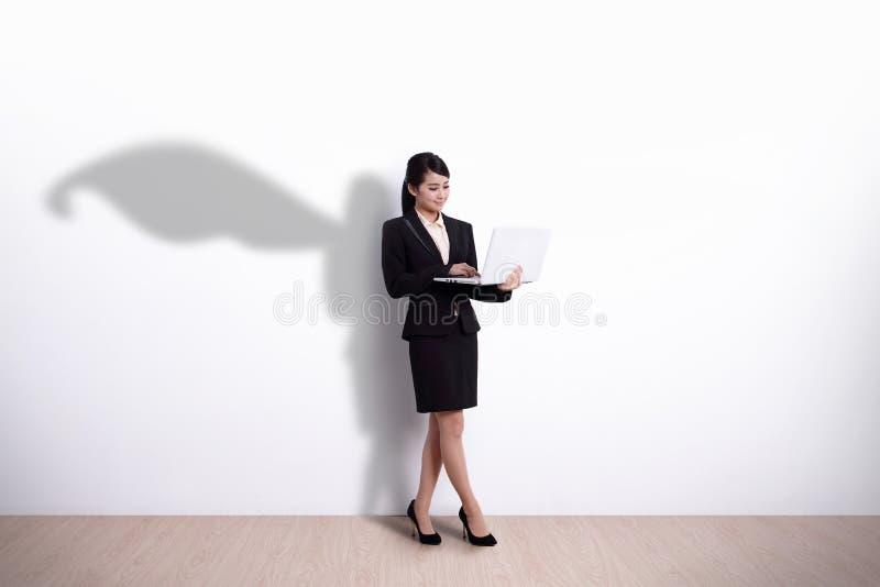 Donna di affari del supereroe con il computer fotografia stock libera da diritti