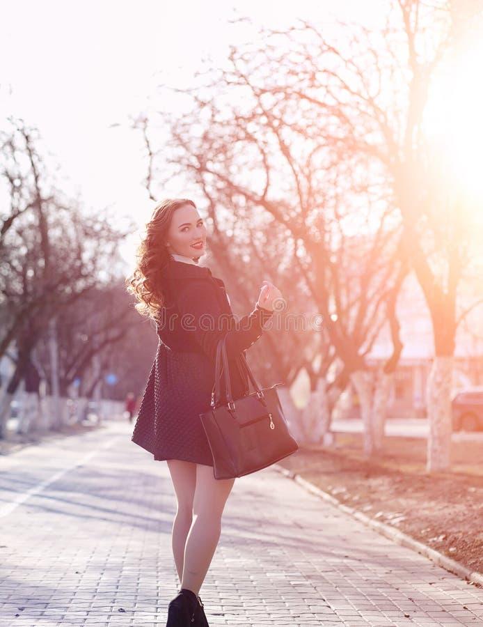 Donna di affari della ragazza in primavera su una passeggiata in un cappotto immagini stock