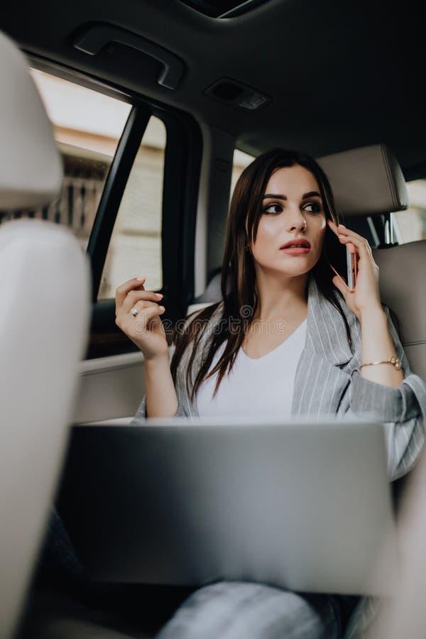 Donna di affari dentro la sua automobile facendo uso di un computer portatile e di un telefono cellulare immagine stock libera da diritti