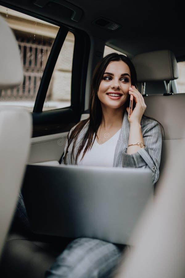 Donna di affari dentro la sua automobile facendo uso di un computer portatile e di un telefono cellulare immagini stock
