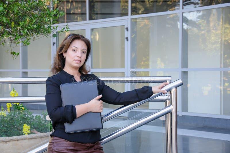 Donna di affari di Atractive con la cassa nera del documento che sta sul Th immagine stock libera da diritti