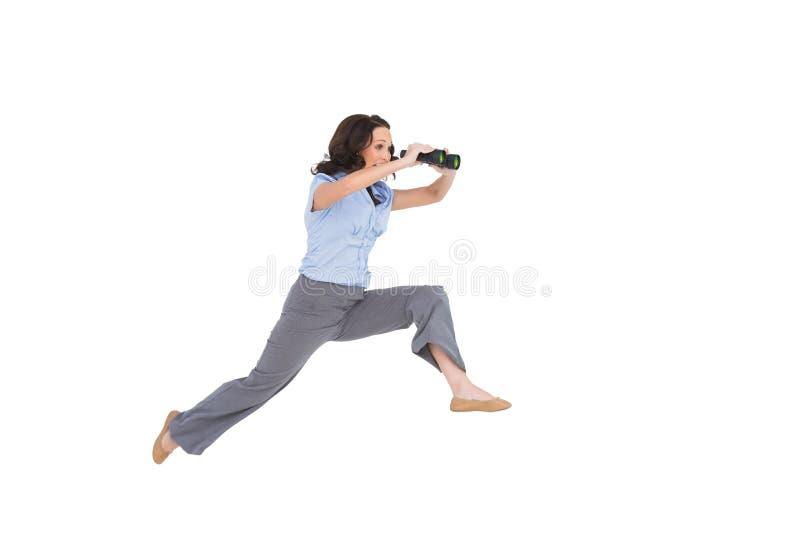Donna di affari di classe allegra che salta mentre tenendo il binocolo fotografie stock