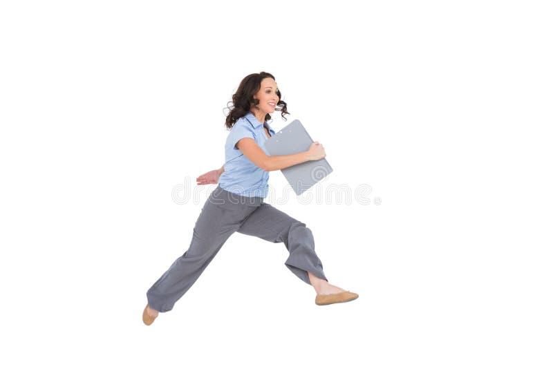 Donna di affari di classe allegra che salta mentre tenendo lavagna per appunti fotografia stock