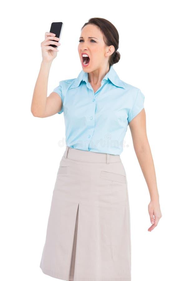 Donna di affari di classe arrabbiata che grida al suo smartphone immagine stock libera da diritti