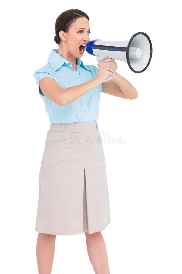 Donna di affari di classe arrabbiata che grida in suo megafono immagine stock