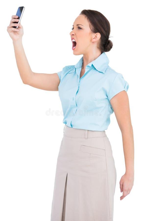 Donna di affari di classe arrabbiata che urla al suo smartphone immagini stock