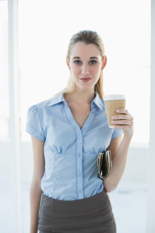 Donna di affari di classe attraente che posa tenendo una tazza e un giornale eliminabili immagini stock libere da diritti