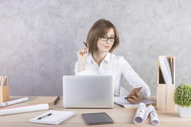Donna di affari di classe che per mezzo dello smartphone immagine stock
