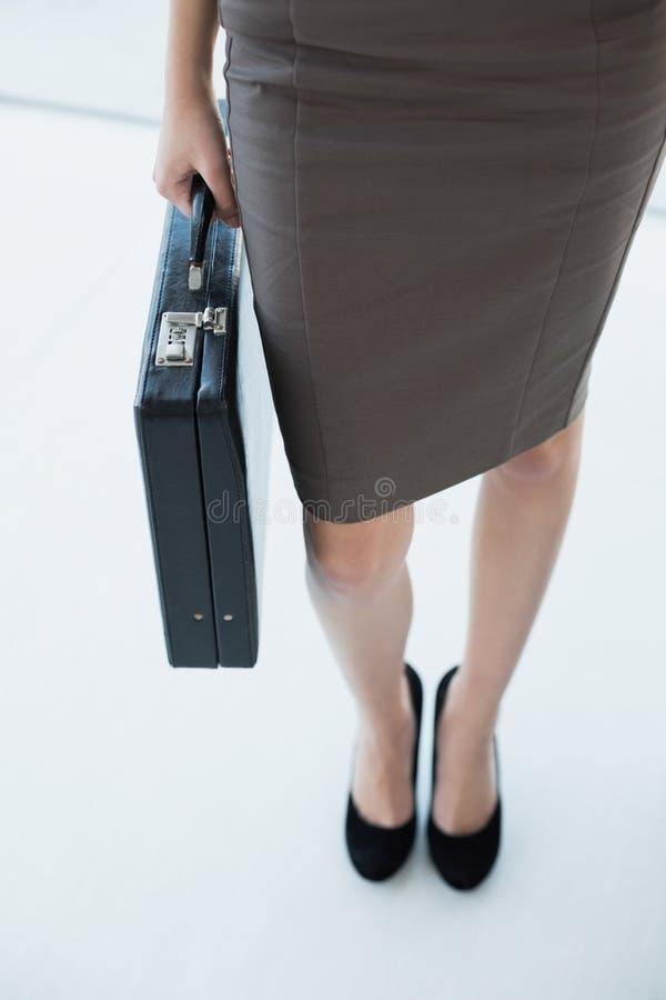 Donna di affari di classe che tiene una cartella nera fotografia stock