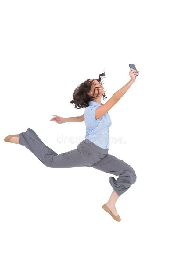 Donna di affari di classe felice che salta mentre tenendo smartphone immagini stock libere da diritti