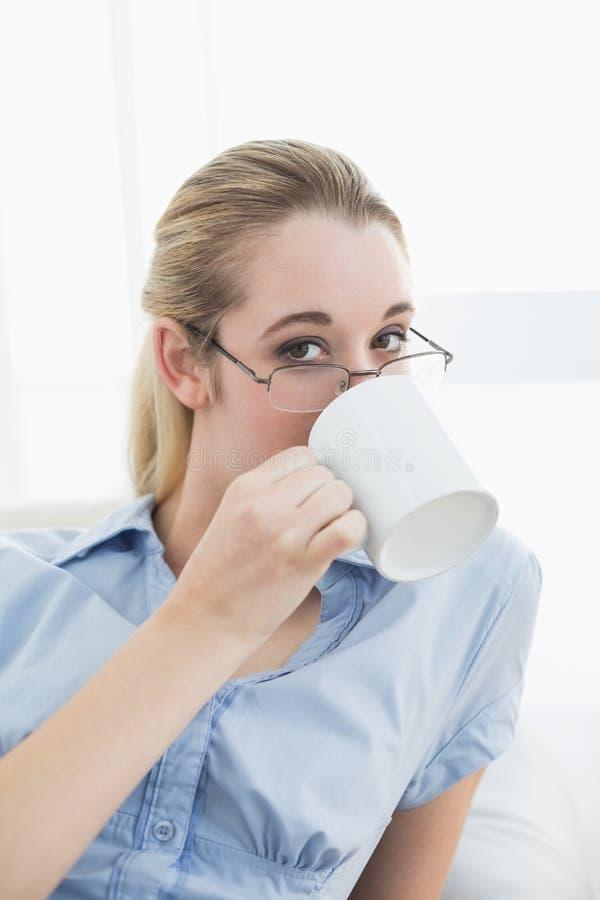 Donna di affari di classe sveglia che si siede sullo strato che beve dalla tazza fotografia stock