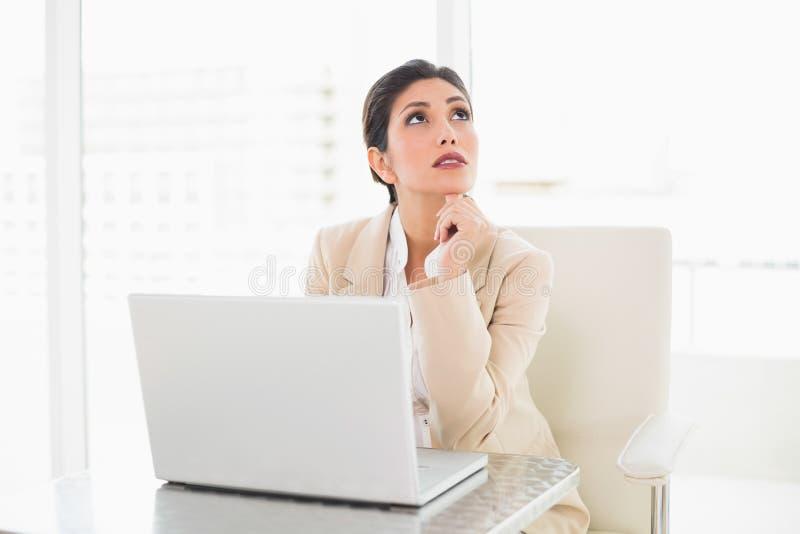 Donna di affari di pensiero che lavora con un computer portatile immagini stock