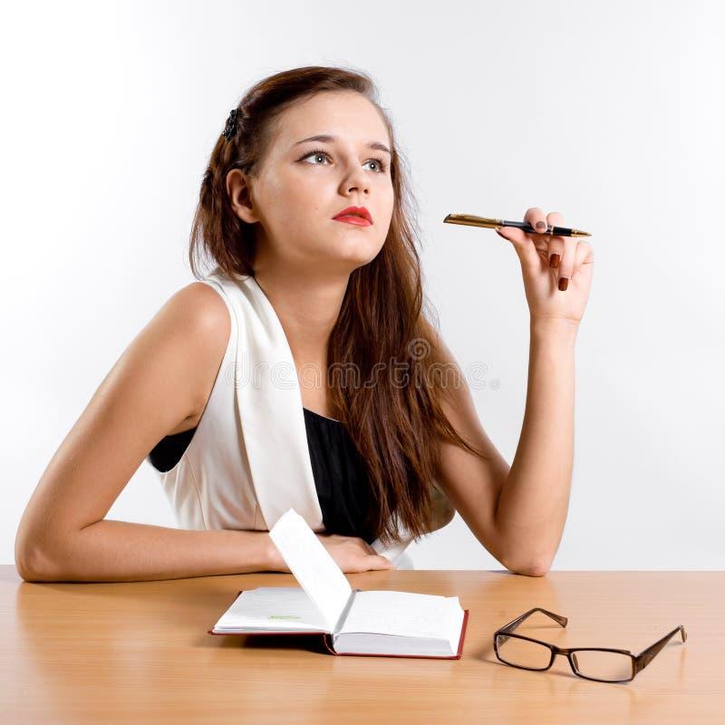 Donna di affari di pensiero che si siede al suo scrittorio immagini stock