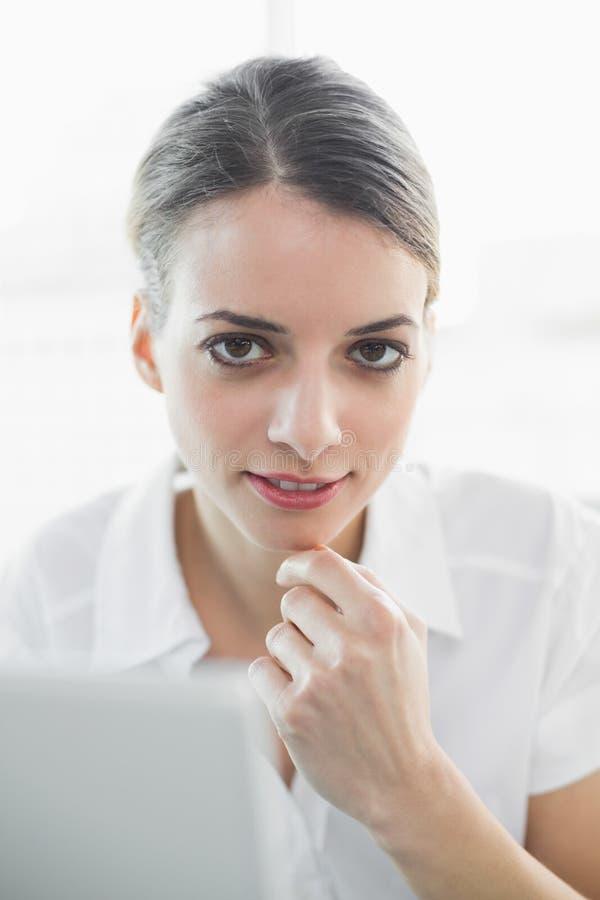 Donna di affari di pensiero contenta che sorride morbidamente alla macchina fotografica fotografia stock