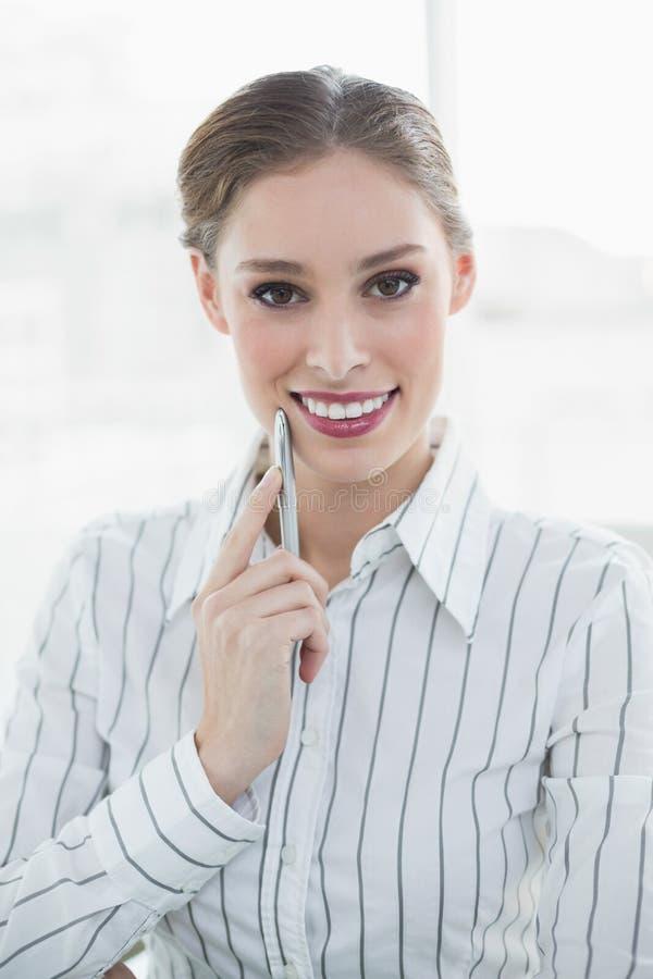 Donna di affari di pensiero sorridente che posa esaminando macchina fotografica immagini stock