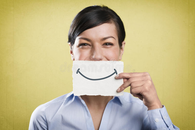 Donna di affari di risata che tiene carta bianca vuota davanti alla sua bocca immagine stock libera da diritti