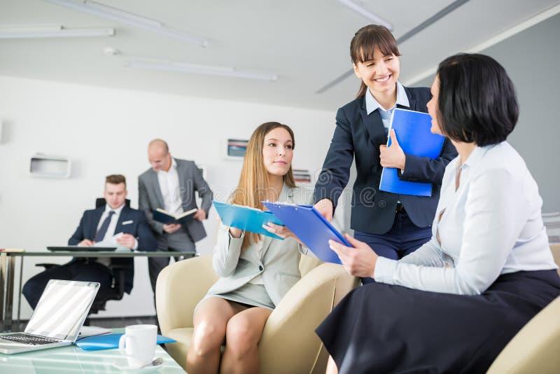 Donna di affari Discussing Over Clipboards in ufficio immagine stock libera da diritti