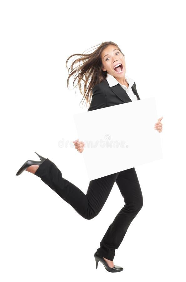 Donna di affari divertente che funziona con il segno del tabellone per le affissioni fotografia stock libera da diritti