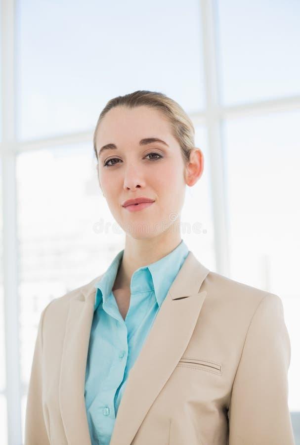 Donna di affari elegante adorabile che posa seriamente nel suo ufficio immagini stock libere da diritti