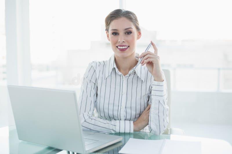 Donna di affari elegante adorabile che si siede al suo scrittorio che tiene una matita immagini stock
