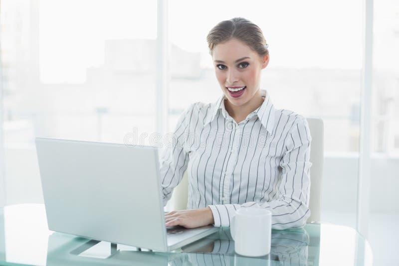 Donna di affari elegante adorabile giuliva che si siede al suo scrittorio facendo uso del suo taccuino immagini stock