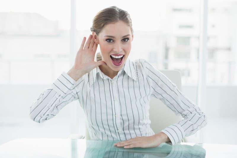 Donna di affari elegante allegra che fa gesto che si siede al suo scrittorio fotografia stock libera da diritti