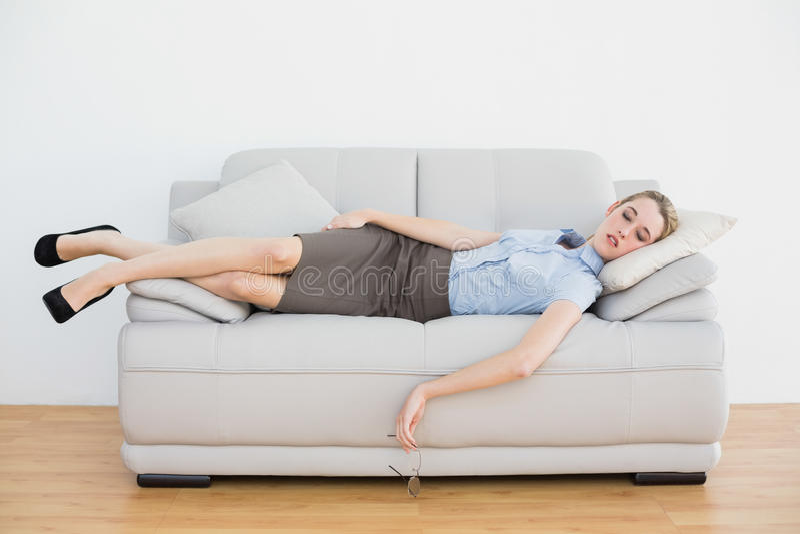 Donna di affari elegante calma che dorme mentre trovandosi sul suo strato fotografie stock libere da diritti