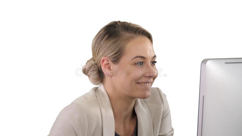 Donna di affari elegante che incoraggia alla scrivania che esamina monitor, fondo bianco fotografia stock