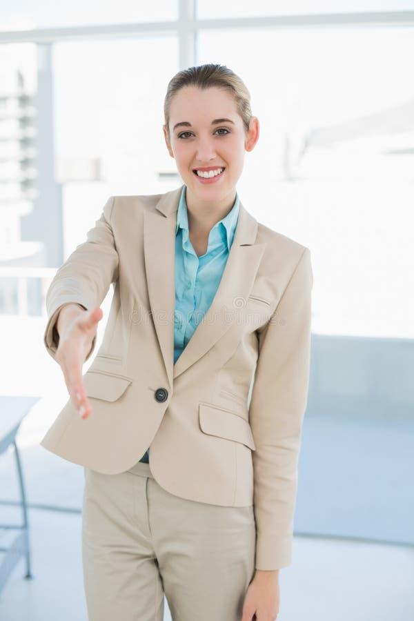 Donna di affari elegante che raggiunge suo sorridere della mano amichevole alla macchina fotografica fotografia stock