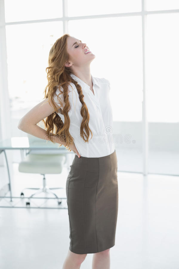 Donna di affari elegante che soffre dal dolore posteriore in ufficio fotografia stock