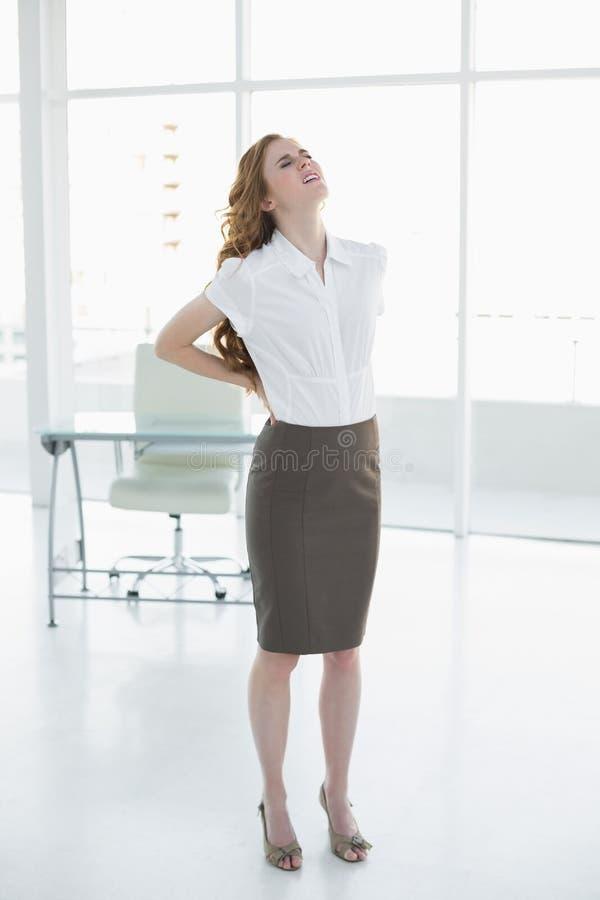 Donna di affari elegante che soffre dal dolore posteriore in ufficio fotografia stock libera da diritti
