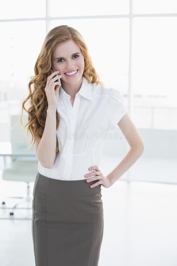 Donna di affari elegante che utilizza telefono cellulare nell'ufficio fotografie stock libere da diritti