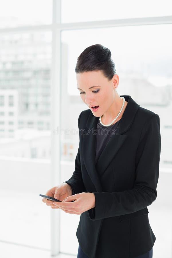 Donna di affari elegante colpita che esamina telefono cellulare immagine stock