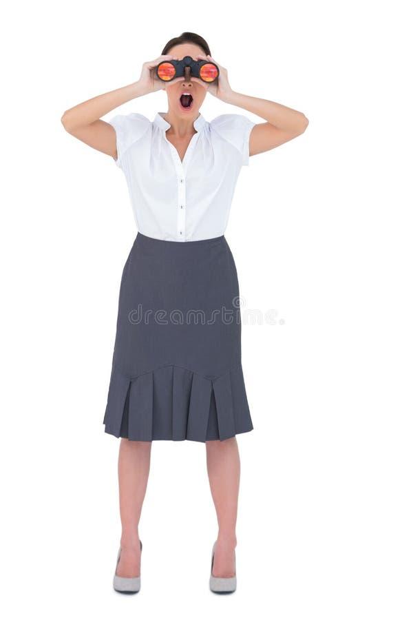 Donna di affari elegante colpita che guarda tramite il binocolo fotografia stock libera da diritti