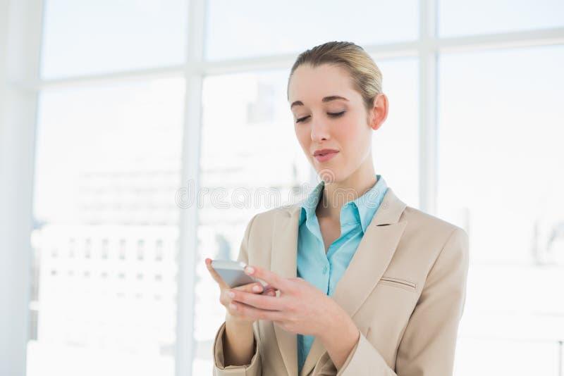 Donna di affari elegante concentrata che manda un sms con il suo smartphone immagini stock libere da diritti