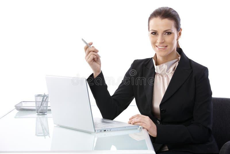 donna di affari elegante dell'Metà di-adulto allo scrittorio fotografie stock