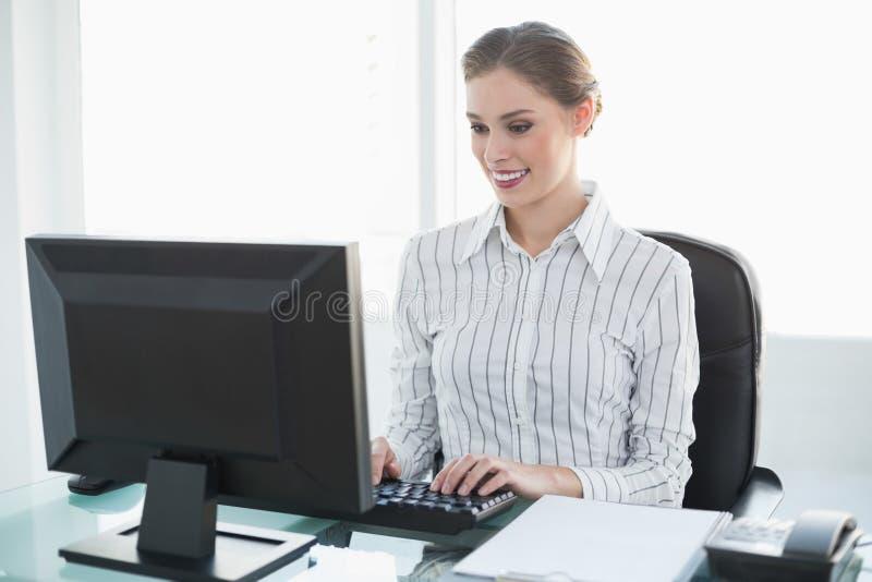 Donna di affari elegante felice che lavora al suo computer immagini stock libere da diritti
